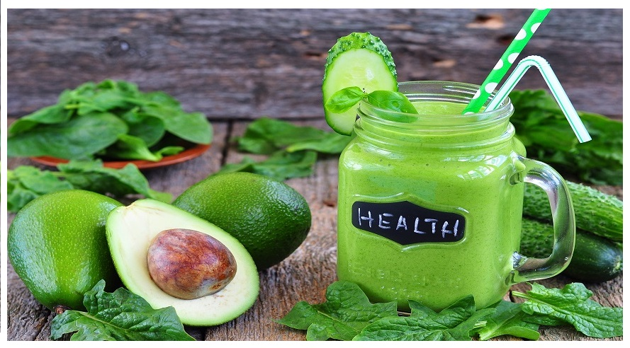 Green vegetable smoothie isolated on wood background