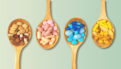 range of supplement pills on wooden spoons