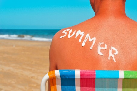 the word summer written with sunblock on the sunburnt back of a man who is sunbathing on the beach