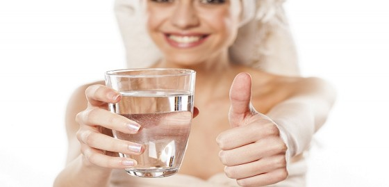 smiling young girl offers a glass of water and showing thumbs up
